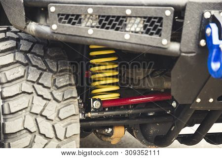 Big Off Road Car Coil Spring. Yellow Shock Absorber On The Car.
