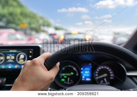 Man Hands Driver On Steering Wheel Of A Modern Car With Car Dashboard And Beautiful Sky Background.t