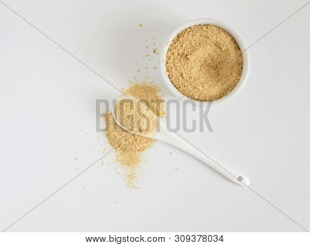 Nutritional Yeast. Nutritional Inactive Yeast In Small White Ctramic Bowl And White Ceramic Spoon. C