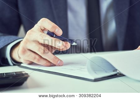 Corporate Man With Pen In Hand Working In Modern Office, Signing Business Document On Desk. Close Up