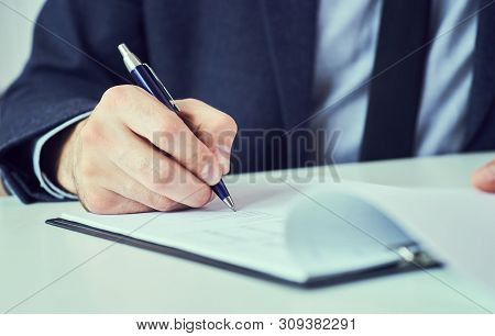 Mid Section Of Businessman In Suit Filling And Signing With Blue Pen Partnership Agreement Form Clip