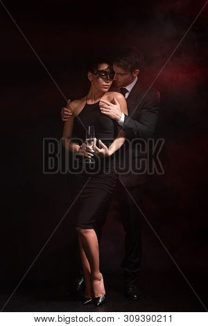 Full Length View Of Sensual Bdsm Couple With Glass On Champagne Embracing On Black