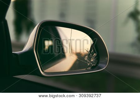 Side Mirror Of The Car With A View Back. Broken Mirror Close Up.