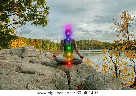 Woman Is Meditating With Glowing Seven Chakras On Stone Outdoor. Woman Is Practicing Yoga On The Lak