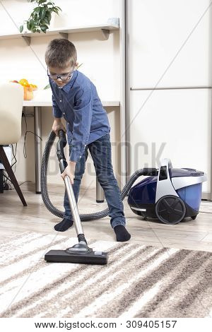Vacuuming A Rug In An Apartment By A Boy Dressed In A Blue Shirt And Jeans Pants.