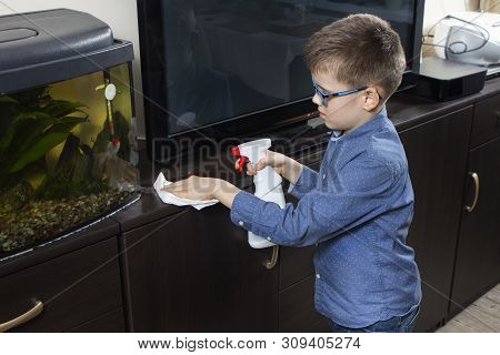 The Boy In A Blue Shirt And Glasses Cleans The Room. Wipes With A White Chicken Cloth. Boy Cleaning