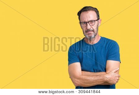 Handsome middle age hoary senior man wearin glasses over isolated background skeptic and nervous, disapproving expression on face with crossed arms. Negative person.