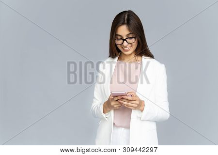 Smiling Indian Young Business Woman Wear White Suit Glasses Using Smartphone App Isolated On Grey Ba