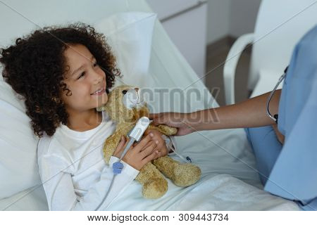 Side view of mixed race female doctor giving teddy bear to child patient in the ward at hospital