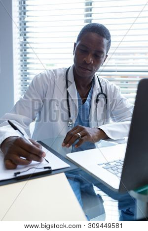 Front view of African-american male doctor writing on a clipboard with a pen at desk in the hospital