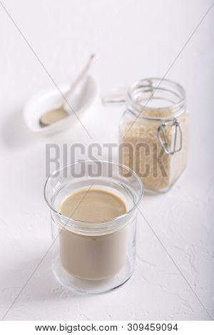 Tahini Sauce In Glass Jar On White Background. Natural Paste Made From Sesame Seeds.
