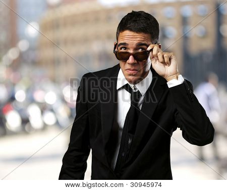 portrait of a business man taking off the sunglasses at a crowded city