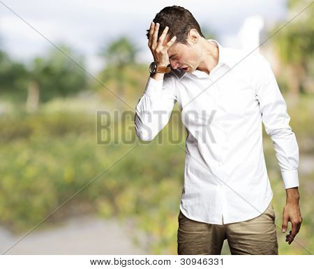 Angry young man doing a frustration gesture at park