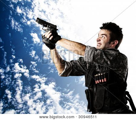 portrait of a young soldier aiming with a gun against a cloudy sky background