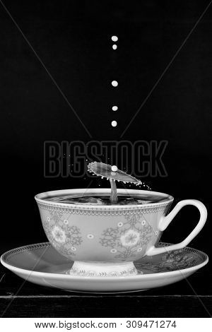 Drops Of Milk Collide To Form An Umbrella Shape In A Cup Of Coffee, Monotone Flash Photography