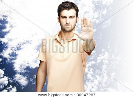 portrait of a handsome young man doing a stop symbol against a cloudy sky background