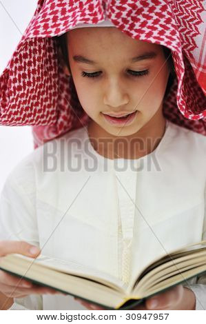 Muslim Arabic little boy reading Qoran