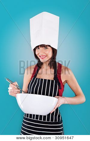 Smiling young woman in a white toque and striped apron holding a whisk and large white bowl