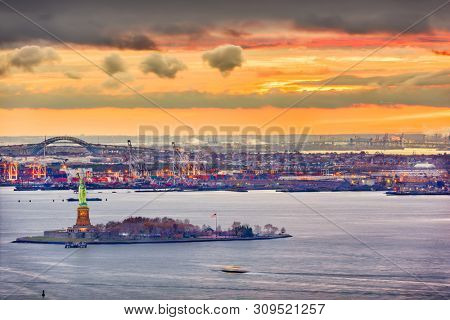 New York Harbor, New York, USA with the statue of liberty and Bayonne, New Jersey in the background.