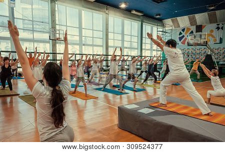 Kyiv, Ukraine: Yoga Class With Active People Performing Some Simple Asanas Together, Training In Spo