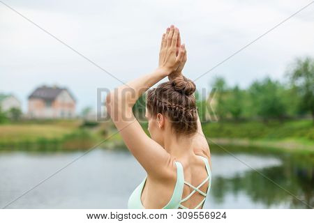 Slim Young Brunette Yogi Performs No Complicated Yoga Exercises On The Green Grass In Summer Against