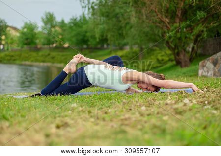 Slender Caucasian Brunette Girl Doing Yoga In Summer On A Green Lawn By The River.