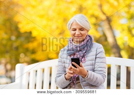 technology, old age and people concept - happy senior woman with smartphone sitting on bench at autumn park