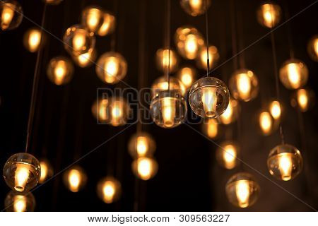 Decorated Electric Garland For Lighting With Bulbs Warm White And Yellow Light On A Dark Background.