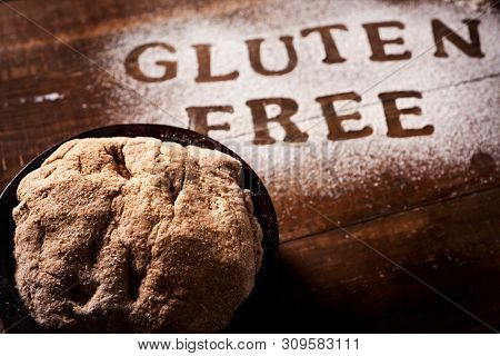 closeup of a piece of dough on a wooden table sprinkled with a gluten free flour where you can read the text gluten free