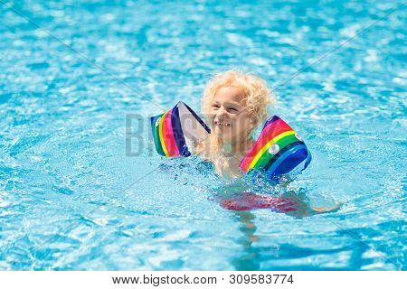 Child in swimming pool wearing colorful inflatable armbands. Kids learn to swim with float aid. Floaties for baby and toddler. Healthy summer outdoor sport activity for children. Water and beach fun. poster