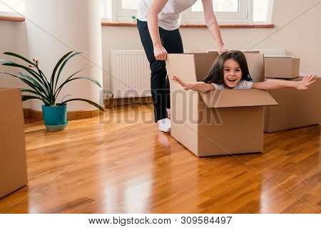 Happy Kid Daughter In Box Excited About Moving Day Or Relocation, Cheerful Girl Playing Unpacking In