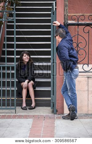 Male flirting with female neighbor sitting on the stairs outside of an apartment complex or condo.  He is confident and charismatic talking to her and depicts dating and relationships. poster