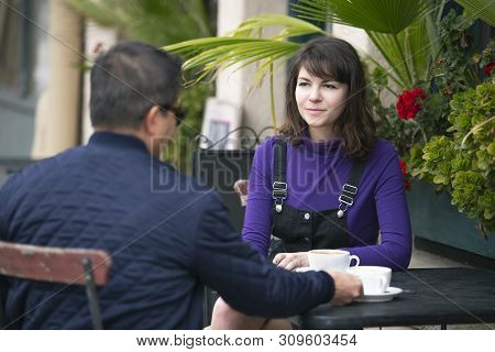 Friends Or Dating Couple Meeting And Hanging Out At An Urban City Sidewalk Cafe.  They Are Sitting O