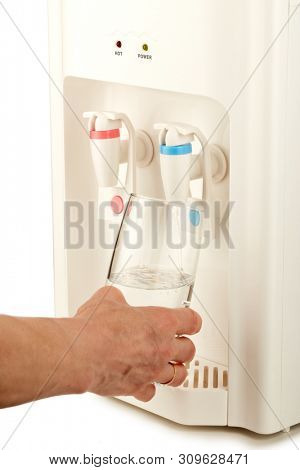 Hand is pouring water into glass from water cooler with big bottle full of purified water isolated on white background. Potable pure water. Water-cooler for office and home. Bottled watercooler