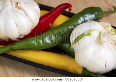 Red, Yellow And Green Hot Pepper And Garlic
