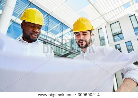 Two architects or engineers at the construction planning with a construction drawing