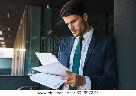 Image of a serious young unshaved handsome business man outdoors at the street near business center holding documents.
