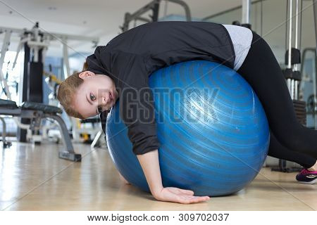 Young Caucasian Woman Lying On Blue Gymnastic Ball Looking Exhausted, Tired, Bored And Weary At The