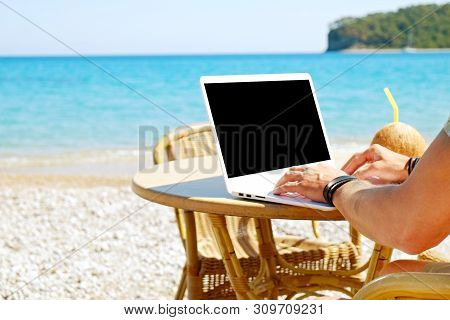 Young Man Working On His Laptop At The Beach At Tropical Destination. Office On The Beach Concept.