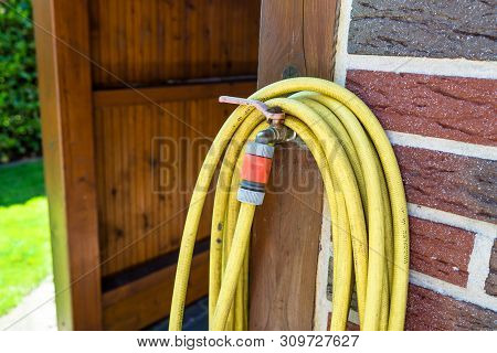 A Garden Yellow Hose Connected To A Tap Protruding From A Farm Building Against A Background Of Bric