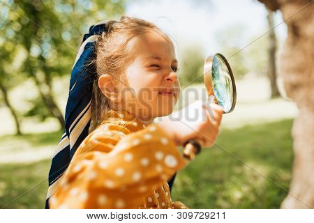 Curious Kid With Magnifying Glass Exploring The Nature Outdoor. Adorable Little Explorer Girl Playin