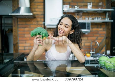 Young Woman With Vegetables Holding Broccoli In Hands Cooking On The Kitchen.