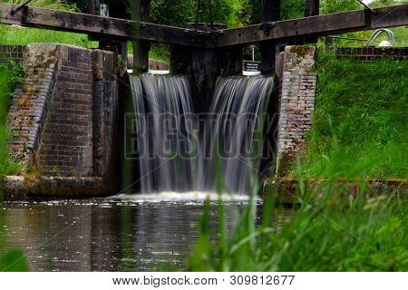 Closed Canal Lock Gates With Excess Water Overflowing With Motion Blur In Aylesbury, Southern Englan