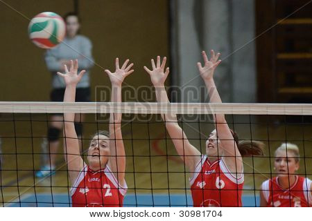 KAPOSVAR, HUNGARY - FEBRUARY 3: Zsanett Pinter (L) in action at the Hungarian Championship volleyball game Kaposvar (red) vs Miskolc (green), February 3, 2012 in Kaposvar, Hungary