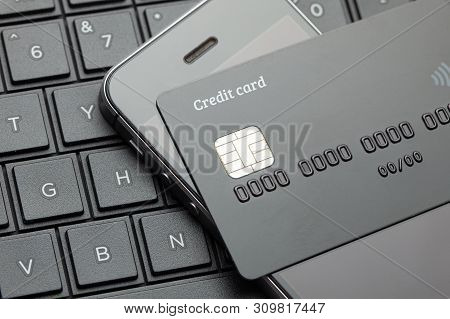 Black Style. Credit Card And Mobile Phone Smartphone On The Keyboard With Laptop. Online Payment For