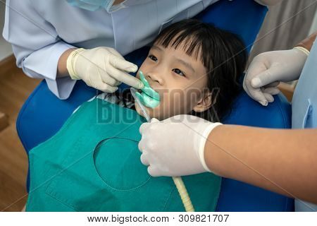 Asian Girl Biting Silicon Tray Of Fluoride And Dental Suction.