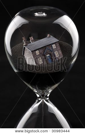 hourglass with house sinking into sand concept for housing market recession or housing difficulties