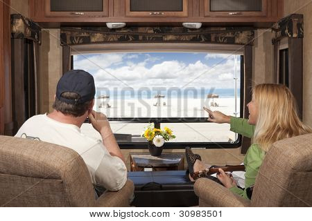 Young Couple Enjoying the Beach View From Their 5th Wheel RV.