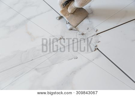 Grouting Tiles Seams With A Rubber Trowel.