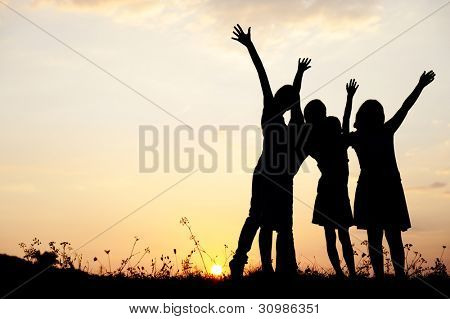 Little girls on meadow at sunset, large copy space